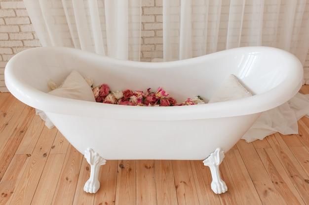 Banheira cheia de flores no interior minimalista com fundo de parede de tijolo
