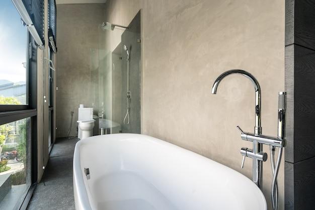 Banheira em villa loft moderno com vidro de janela de espaço aberto