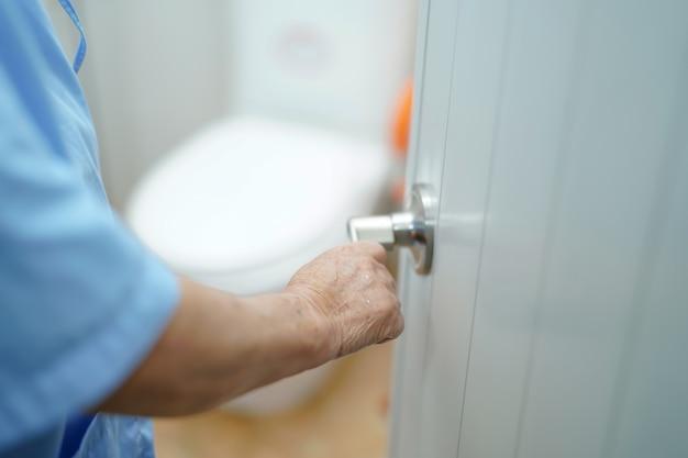 Banheiro aberto asiático do toalete do paciente sênior da mulher no hospital.