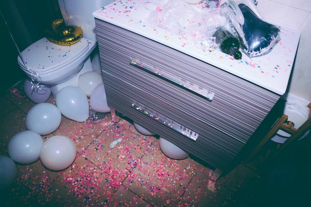 Banheiro bagunçado com uma garrafa vazia; confetes coloridos e balões brancos após a festa de aniversário