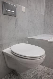 Banheiro branco e limpo com paredes de pedra em um banheiro