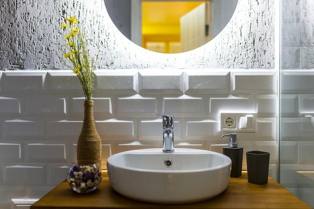 Banheiro com azulejos brancos em um pequeno apartamento moderno