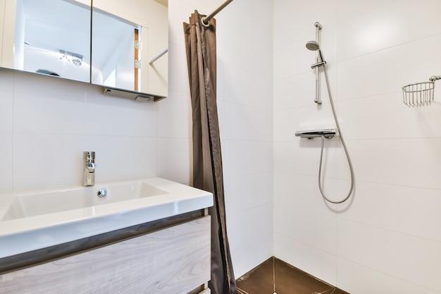 Banheiro com paredes de azulejos brancos e chuveiro aberto perto do armário baixo da pia com luz