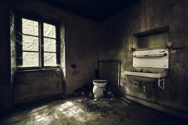 Banheiro com pia na parede coberto de sujeira sob as luzes em um prédio abandonado