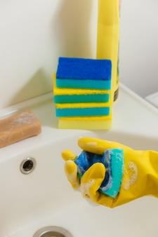 Banheiro da limpeza com detergente em luvas de borracha amarelas com esponja azul - trabalhos domésticos, conceito da limpeza da primavera.
