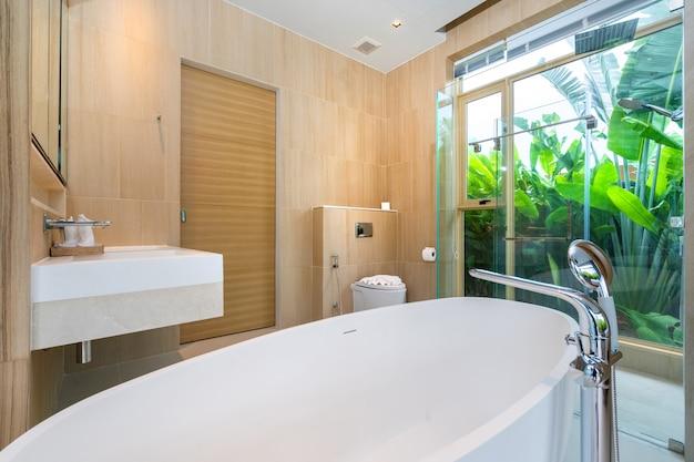 Banheiro de luxo possui banheira com jardim esverdeado
