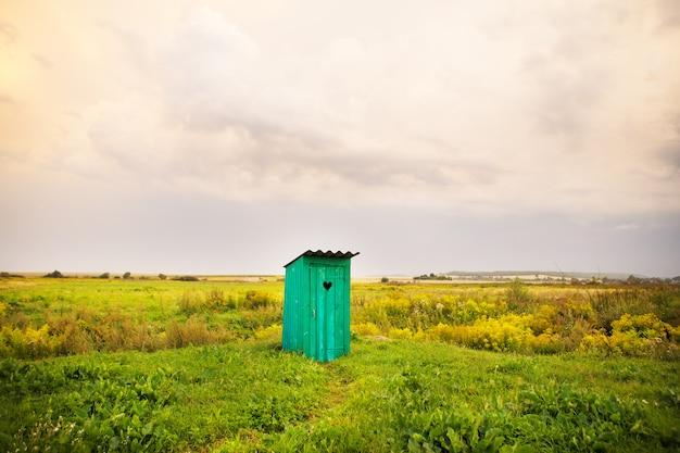 Banheiro de madeira com uma janela esculpida em forma de coração, um campo aberto