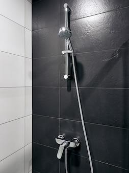 Banheiro e chuveiro no hotel com paredes cinza e brancas