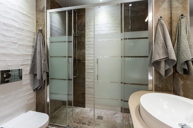 Banheiro em estilo moderno com ladrilhos texturizados no chão e nas paredes dois chuveiros com porta de vidro com ...