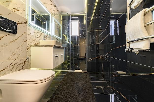 Banheiro luxuoso e espaçoso em tons de preto e branco com banheira vitoriana e box amplo