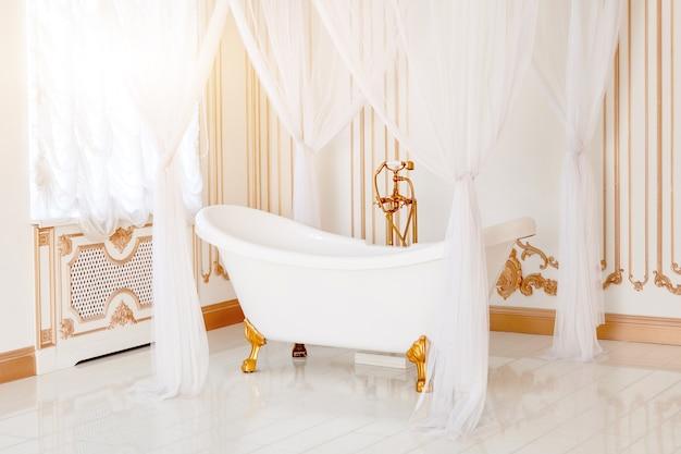 Banheiro luxuoso em cores claras com detalhes de móveis dourados e copa