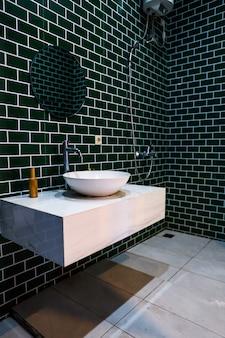 Banheiro minimalista com padrão de tijolo preto e piso branco