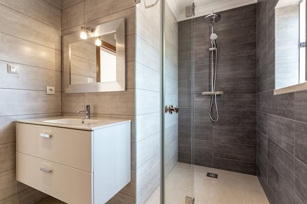 Banheiro moderno com chuveiro e pia para higiene.