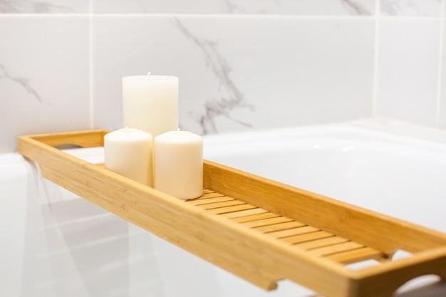 Banheiro moderno com mesa de madeira e velas. vista lateral da parede de fundo de mármore branco