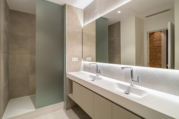 Banheiro moderno com piso frio, área de chuveiro, duas pias e um grande espelho de parede