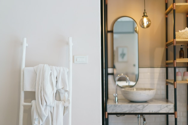 Banheiro moderno, espelho com lâmpadas luminosas e pia, escada toalheiro.