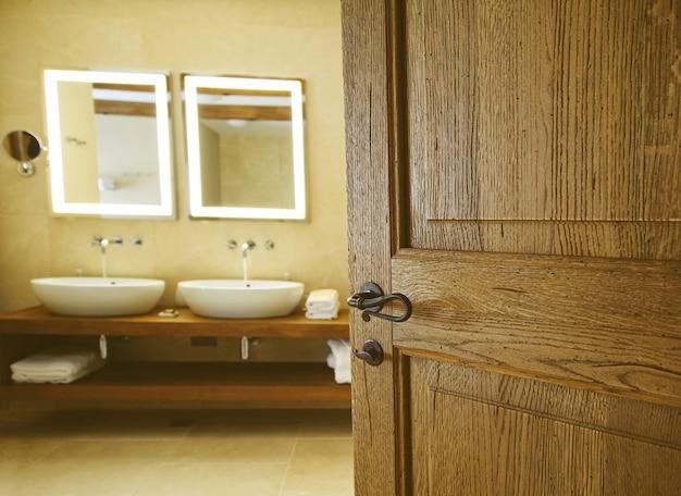 Banheiro para uma porta de madeira aberta.