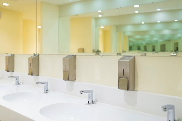 Banheiro público moderno com lavatório e espelhos