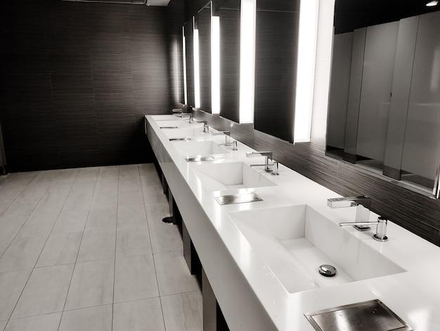 Banheiro público vazio com lavatórios, trocador de bebê e vasos sanitários no espelho. linha branca da pia com espelhos e luzes. vista superior horizontal copyspace