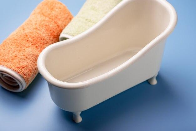 Banho de brinquedo vazio com toalhas sobre um fundo azul. o conceito de limpeza, higiene.