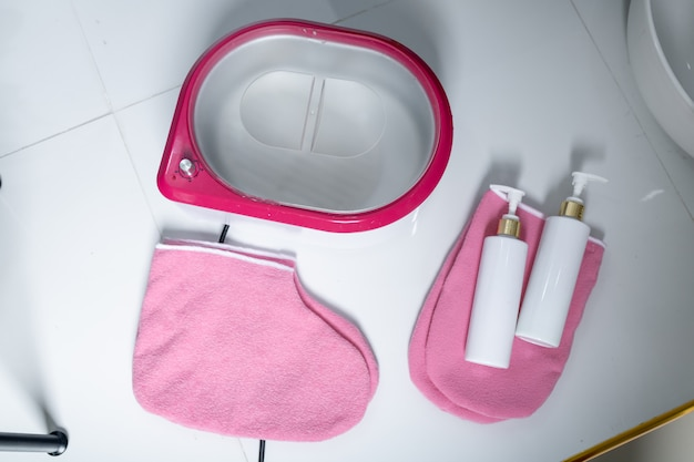 Banho de pé-de-rosa com garrafas brancas em meias-de-rosa para uma pedicure em um fundo de flor