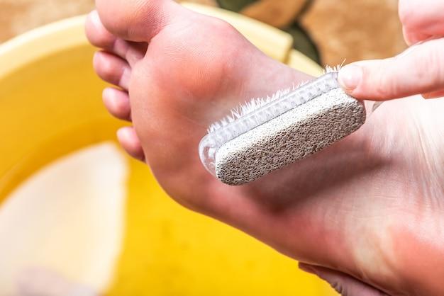 Banho de pés. cuidar da pele seca dos pés e calcanhares. usando ferramentas de pedicure com pedra-pomes e uma escova.