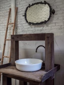 Banho de pia limpa branca e torneira na mesa de madeira vintage e espelho vintage na parede de tijolo branco