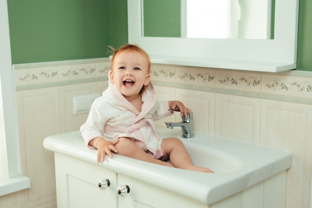Banho e higiene do bebê. cuidar de crianças pequenas. linda garota encantadora de 1 ano em um roupão branco senta-se na pia no banheiro