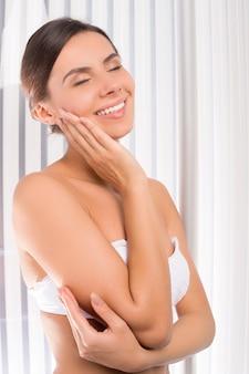 Banhos de sol no solário. mulher jovem e atraente em pé na cabine de bronzeamento e tocando o rosto