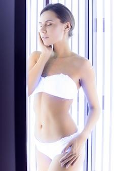 Banhos de sol no solário. mulher jovem e atraente em pé na cabine de bronzeamento e tocando seu rosto