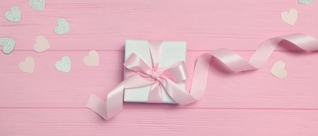 Banner caixa de presente com fita e confetes em forma de coração no fundo rosa de madeira com lugar para o seu texto.