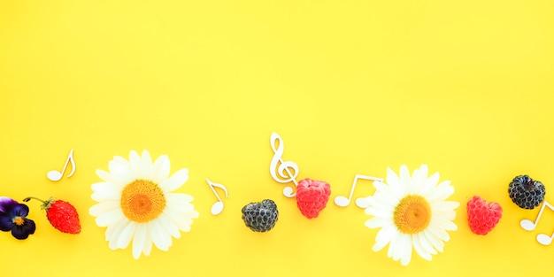 Banner clave de sol e notas musicais com flores e frutos em um fundo amarelo.