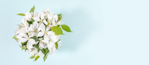 Banner com buquê de galhos de macieira branca florescendo em azul claro