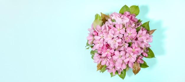 Banner com buquê de macieira rosa florescendo ou galhos de sacura em azul claro.