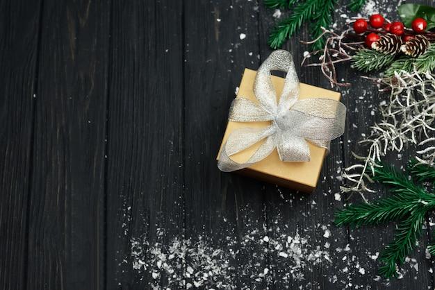 Banner com caixa de presente e decoração de árvore para o feriado de natal e ano novo no inverno com neve sobre um fundo de madeira