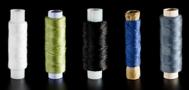 Banner com diferentes fios de seda brilhantes para costura, isolados em um fundo preto. plano de fundo para um bordado e banner de costura.