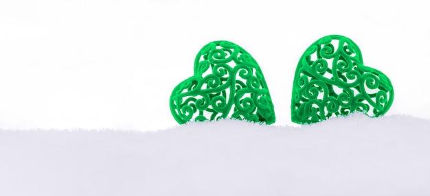 Banner com dois corações de veludo verde em um monte de neve