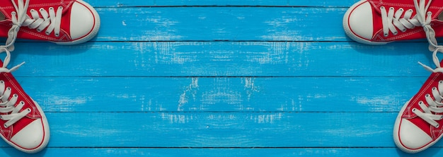 Banner com dois pares de sapato vermelho da juventude em uma superfície de madeira azul