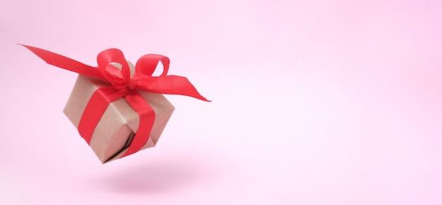 Banner com fita vermelha de caixa de presente em rosa.