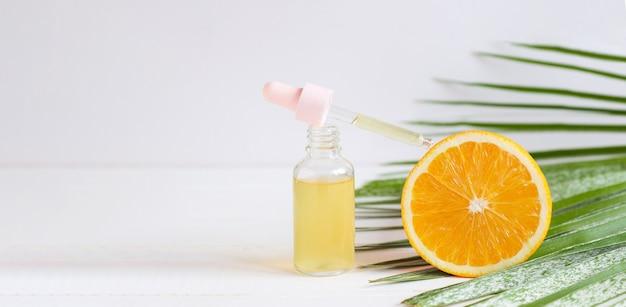 Banner com frasco de soro cosmético para a pele com conta-gotas laranja e folha de palmeira conceito de spa de beleza