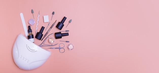 Banner com lâmpada de manicure e ferramentas para aplicação de verniz superior em um fundo colorido. foto do conceito de manicure do salão de beleza