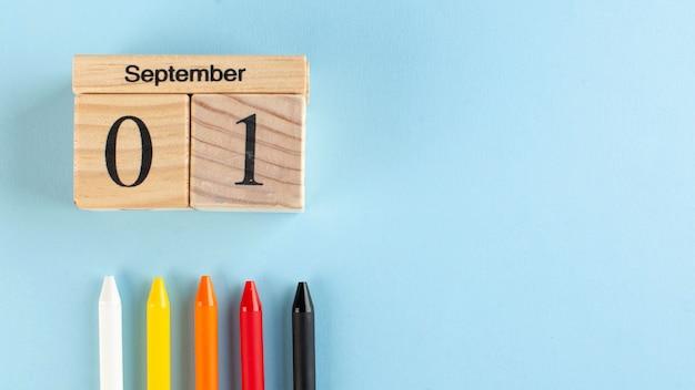 Banner com um calendário de madeira de 1º de setembro, canetas coloridas sobre fundo azul. copie o espaço. começo do ano escolar