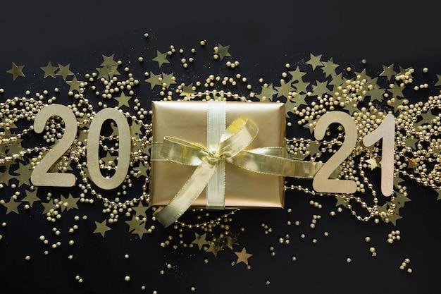 Banner criativo brilhante de natal com presente dourado e data de ano novo de 2021 no espaço preto