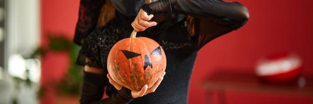 Banner da menina com máscara em casa com fantasia de halloween com a abóbora jack ou laurent