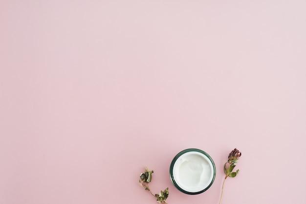 Banner da web. creme para a pele e flores secas, folhas. fundo de mesa branca. cosméticos orgânicos, conceito de spa. espaço vazio, vista plana, vista superior. creme cosmético e flores secas em fundo rosa pastel
