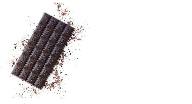 Banner de barra de chocolate amargo com aparas de vista superior isolada na superfície branca com espaço de cópia