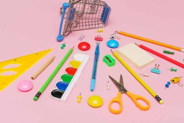 Banner de carrinho com avaliações escolares em fundo rosa de volta ao conceito de escola vários artigos de papelaria para ...