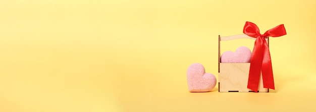 Banner de corações rosa e caixa de madeira na superfície amarela