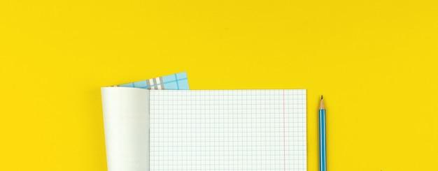 Banner de educação com caderno escolar aberto com papel de matemática quadriculado e lápis no fundo da mesa amarela, espaço de cópia e foto da vista superior