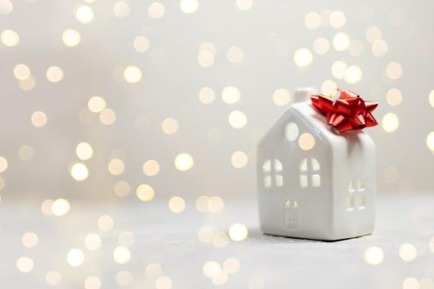 Banner de feliz ano novo com uma pequena casa modelo de brinquedo com laço vermelho